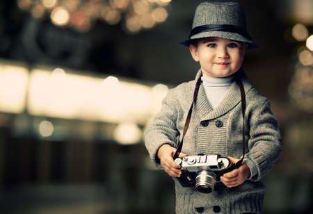 an adorable: Baby boy with retro camera over blurred background. Stock Photo