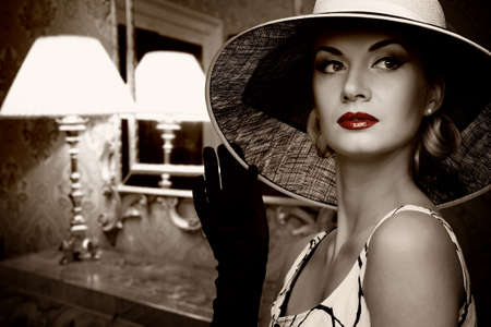 Beautiful woman in hat in luxury interior. photo