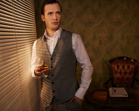 Retro man with a glass standing near window. Stock Photo - 12221688
