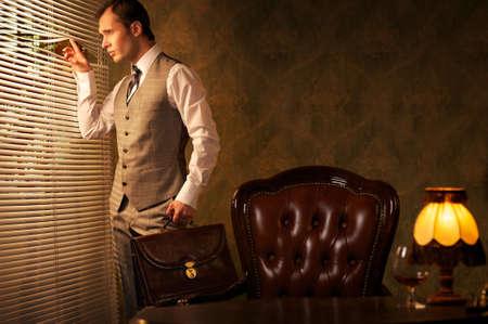 vest: Retro man with a briefcase looking through jalousie.