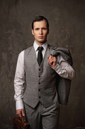 the vest: Businessman with a briefcase on grey background. Stock Photo