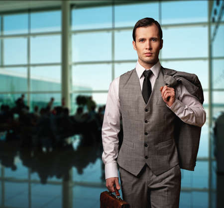 gray suit: Man with a briefcase in an airport.
