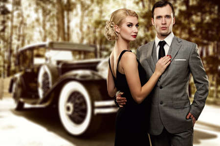 mafia: Retro couple against old car.