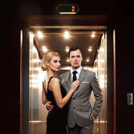 Retro pareja de pie contra el ascensor.