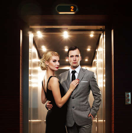 people in elevator: Retro couple standing against elevator.