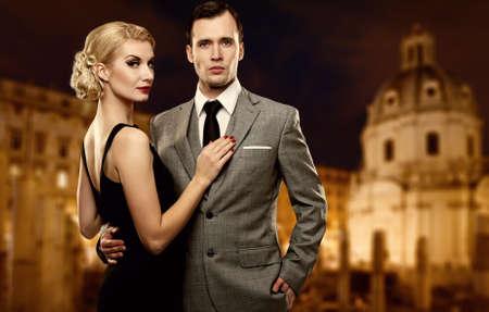 donne eleganti: Coppia Retro contro panorama notturno della citt�.