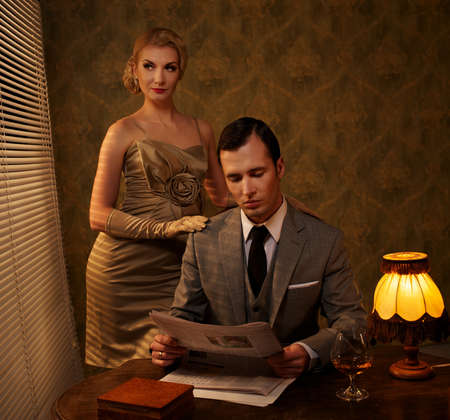 Man in suit reading newspaper with woman behind him. Stock Photo - 12609148