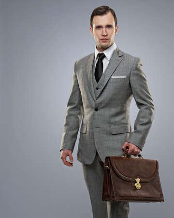 Businessman with a briefcase on grey background. Stock Photo - 12609140