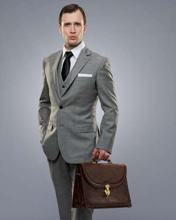 suit tie: Businessman with a briefcase isolated on grey.