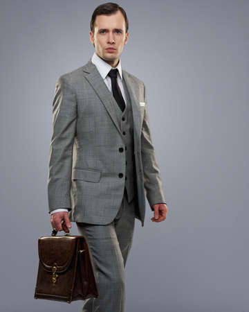 Businessman with a briefcase isolated on grey. Stock Photo - 12609171