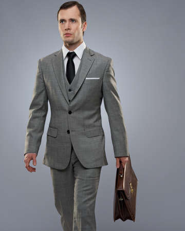 Businessman with a briefcase isolated on grey. photo