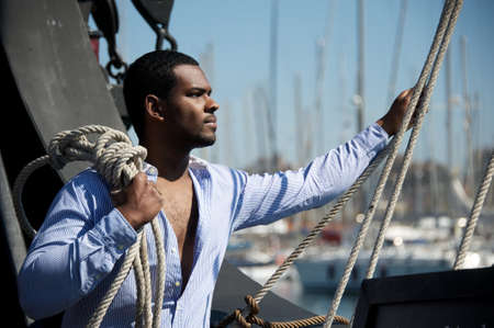 afroamerican: Handsome afro-american sailor against boats