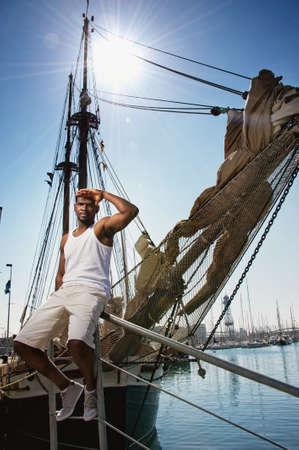 Handsome afro-american man against boat in port Banco de Imagens