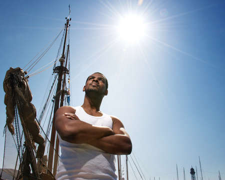 Handsome afro-american man against boat photo