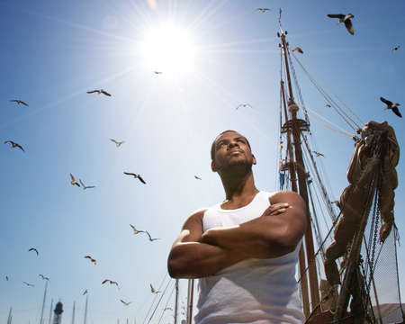 Handsome afro-american man against boat's mast. photo