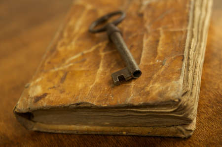 rare: Old metal key on vintage book. Stock Photo