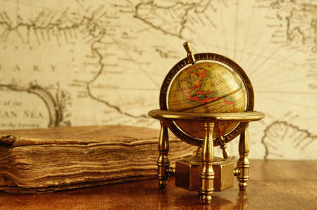 Globe and vintage book against map on a wall