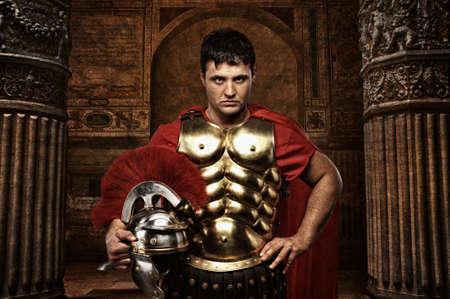 soldati romani: Soldato romano contro l'antico edificio. Archivio Fotografico