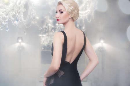 chandelier background: Beautiful woman in luxury interior  Stock Photo