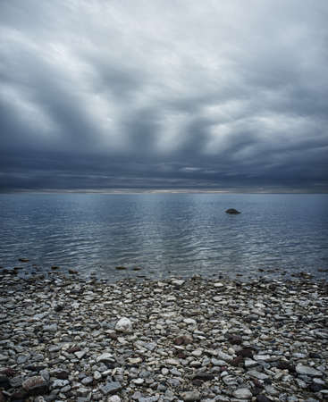 Moody sky over rocky beach photo