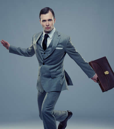 jump suit: Businessman with a briefcase isolated on grey