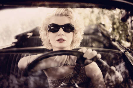 Retro woman behind steering wheel photo