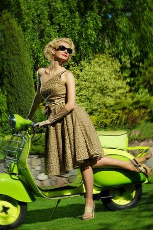 Frau im Retro-Kleid mit einem Motorroller Standard-Bild