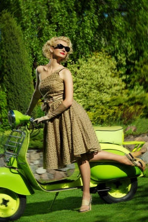 Woman in retro dress with a scooter Stock Photo