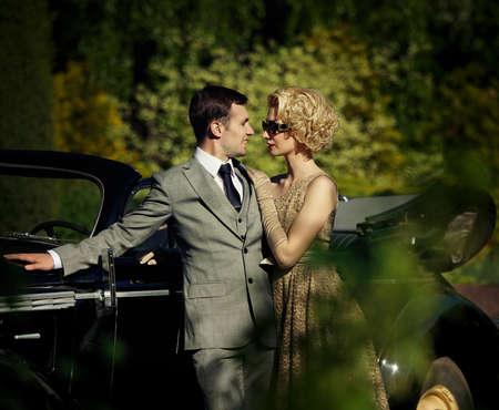 mujer con corbata: Pareja al aire libre, cerca de un coche retro