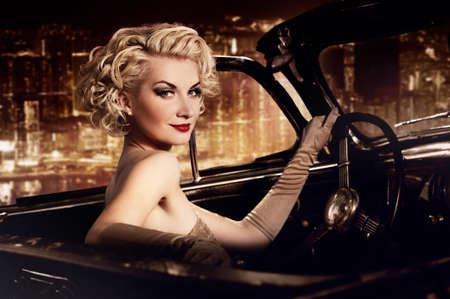 cabrio: Vrouw in retro auto tegen de nacht stad. Stockfoto