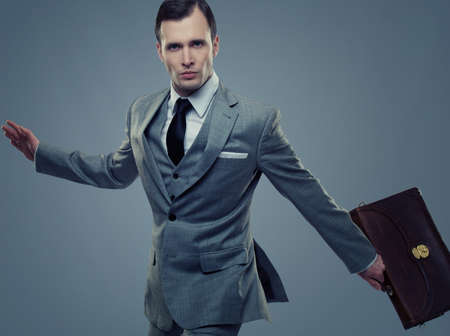 Businessman with a briefcase isolated on grey Stock Photo - 13809519