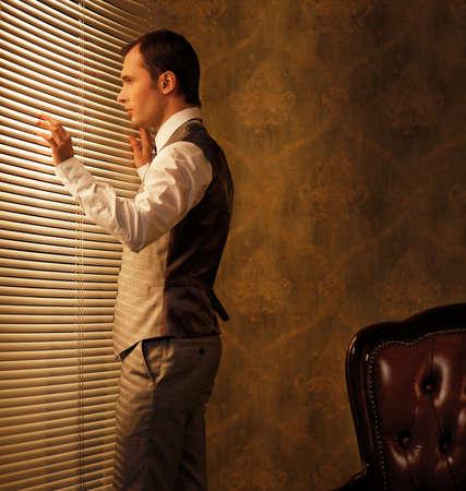 Man looking through jalousie Stock Photo - 14075242