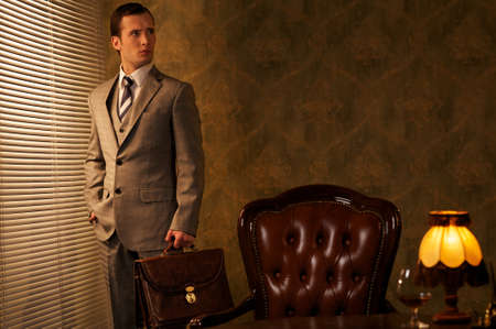 Businessman with a briefcase in retro interior photo