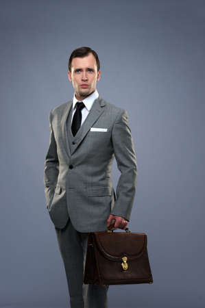 Businessman with a briefcase isolated on grey Stock Photo - 14075260