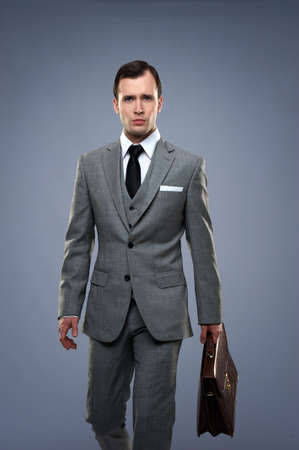 Businessman with a briefcase isolated on grey Stock Photo - 14075252