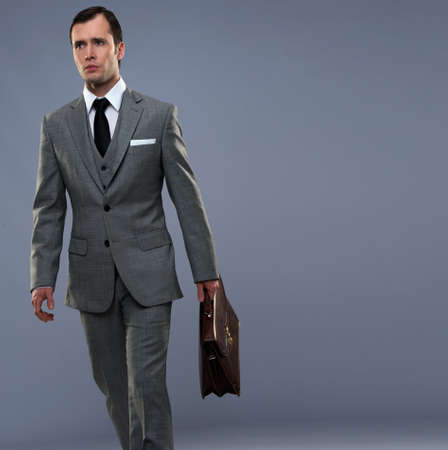 Businessman with a briefcase isolated on grey photo