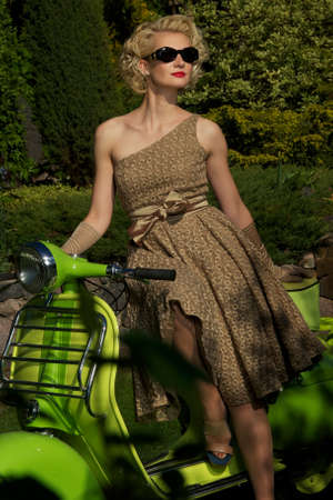 Woman in retro dress with a scooter Stock Photo - 14075251