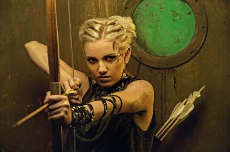 arco y flecha: Mujer con un arco en un búnker