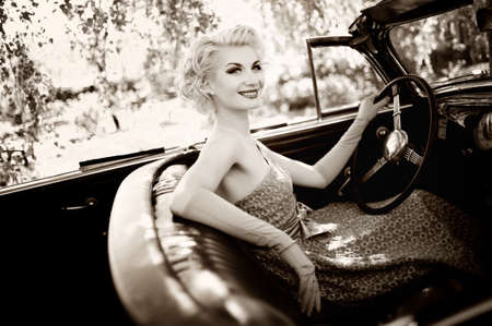 Smiling retro woman in convertible photo