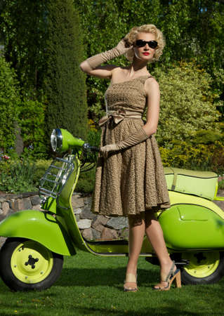 Woman in retro dress with a scooter Stock Photo - 14082199