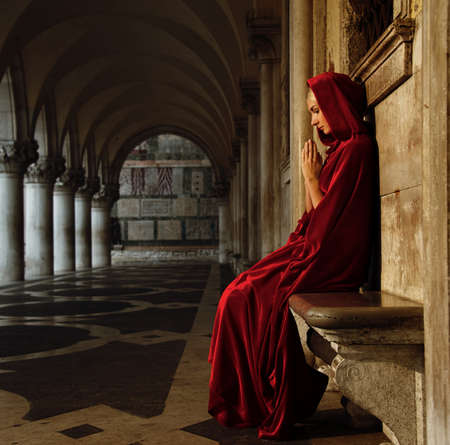 jesus hands: Woman in red cloak praying alone