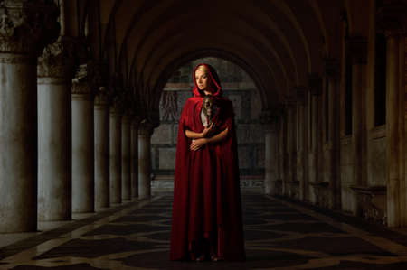Woman with a mask wearing red cloak outdoor photo