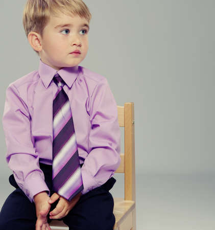 Thoughtful baby boy sitting on a chair photo