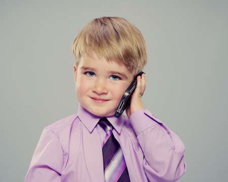 calling on phone: Baby boy in a purple shirt with a cell phone