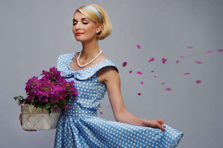 Lovely woman in a blue dress with a basket of flowers photo