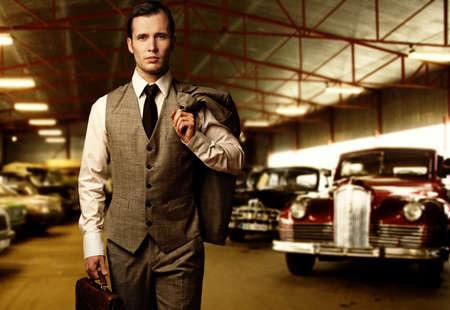 金持ち: ガレージでブリーフケースを持ったビジネスマン