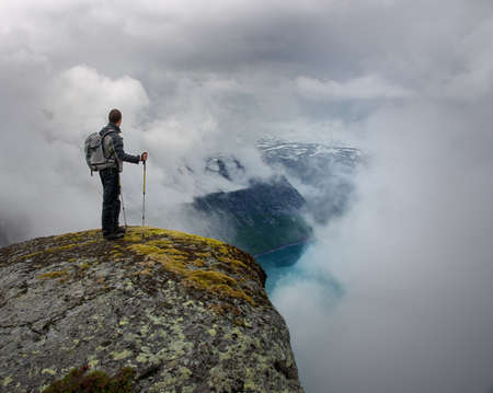 norge: Man with hiking equipment standing on rocks edge
