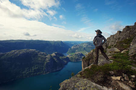 Man hiker looking over fjord panorama photo