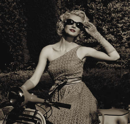 retro woman: Woman in retro dress with a scooter Stock Photo