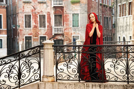 Beautiful woman in red cloak on a bridge photo